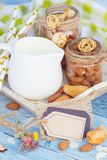Almonds and jar with milk on the wooden tray Stock Images