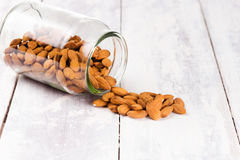 Almonds in a jar, spilled on a white vintage table. Royalty Free Stock Image
