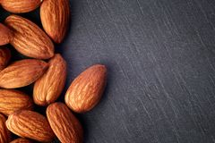 Almonds kernel. On dark rustic background. Top view with copy space stock images