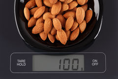 Almonds on kitchen scale Stock Photography
