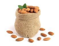 Almonds with leaf in bag from sacking isolated on white background.  Stock Image