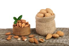 Almonds with leaf in bag from sacking on a wooden table with a white background.  Royalty Free Stock Image