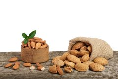 Almonds with leaf in bag from sacking on a wooden table with a white background Royalty Free Stock Photo