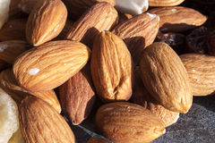 Almonds. Light brown almonds, on a stone plate Royalty Free Stock Images