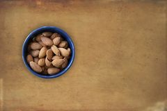Almonds lying in a blue bowl with brown grunge background. Top view image with blank copy space for text. Almonds lying in a blue bowl with brown grunge royalty free stock image