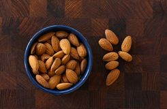 Almonds lying in a blue bowl on dark wooden background with almonds scattered around. Top view image. Almonds lying in a blue bowl on dark wooden background with royalty free stock photo