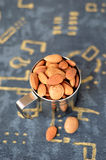 Almonds in a metal mug on textile background Royalty Free Stock Image