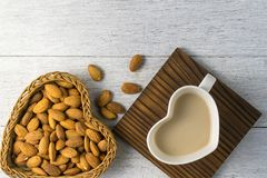 Almonds milk with almonds in heart shape basket. On white wooden Stock Image