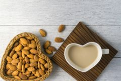 Almonds milk with almonds in heart shape basket Stock Photos