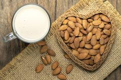 Almonds milk with almonds in heart shape basket. On wooden Stock Photo
