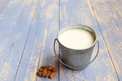 Almonds milk in aluminum can isolated on wooden background. Raw vegan fresh bio milk for healthy life. Healthy life concept stock image