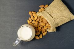 Almonds milk with almonds in sackcloth. Black wooden Stock Images
