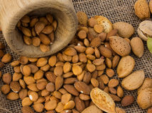 Almonds in a mortar. Scattered on the table. burlap background Stock Photography