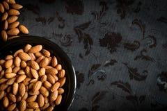 Almonds nut in black plate on dark background Stock Image