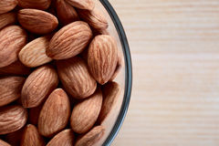 Almonds nuts. Glass bowl with almonds nuts on cutting board royalty free stock photos