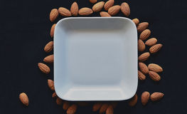 Almonds outside white plate against black background Royalty Free Stock Images