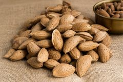 Almonds. Peeled in a bowl or in their nutshell on sackcloth Royalty Free Stock Photography