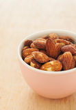 Almonds in a pink bowl on wooden background Royalty Free Stock Photo