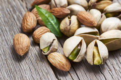 Almonds and pistachios with leaf Royalty Free Stock Image