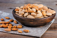Almonds and pistachios on a wooden bowl. Royalty Free Stock Photo