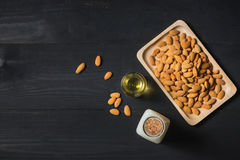 Almonds in plate and milk bottle on wooden background. Almond nu stock photo