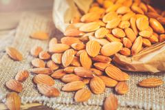 Almonds, poured out of a paper bag. Almonds, pour out on wooden table out of a paper bag. Healthy eating Royalty Free Stock Photo