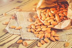 Almonds, poured out of a paper bag. Almonds, pour out on wooden table out of a paper bag. Healthy eating Stock Photography