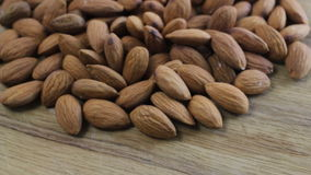 Almonds rotating on wooden table close up stock video