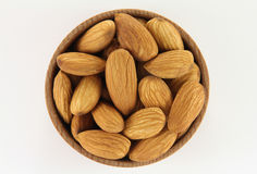 Almonds in a round wooden form. On a white background Royalty Free Stock Photography