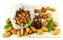 Almonds in the sack and almond oil. On mat isolated on white background Stock Image