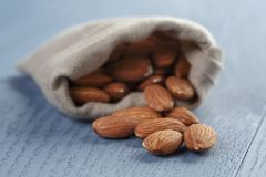 Almonds in sack bag on blue wood table Stock Photography