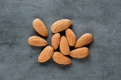 Almonds scattered over dark stone board Royalty Free Stock Photo