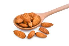 Almonds seeds in wooden spoon isolated on white royalty free stock photography