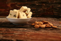 Almonds served with flaky Indian dessert - Soan Halwa, Royalty Free Stock Photos