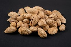 Almonds  in shell. Heap of almonds in shell isolated on black. Raw food ingredients Royalty Free Stock Photography
