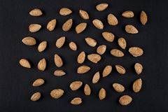 Almonds  in shell. Heap of almonds in shell isolated on black. Raw food ingredients Royalty Free Stock Photos