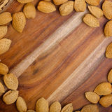Almonds in shells bordering wooden table. Space. Almonds nuts in shells bordering wooden table. Space for text Stock Photography