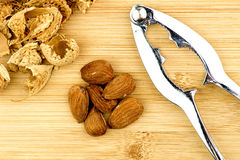 Almonds, shells with metal nut cracker on wooden background Royalty Free Stock Images