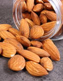 Almonds spilling out of glass jar on concrete structure Royalty Free Stock Images