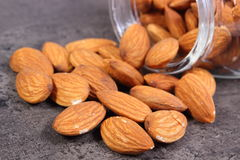 Almonds spilling out of glass jar on concrete structure Royalty Free Stock Image