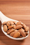 Almonds on spoon. On a wooden background.  Side lightening Royalty Free Stock Photo