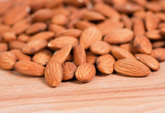 Almonds spread on a wooden table. Top Stock Image