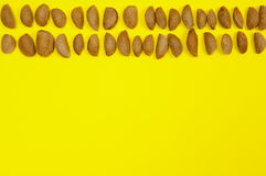 Almonds in two rows on yellow background with copy space Stock Photography