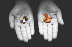 Almonds versus pills. Stock Photos