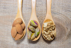 Almonds, walnuts and pistachio on a wooden spoon. Royalty Free Stock Images