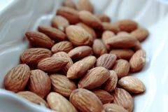 Almonds. In a white bowl Stock Photos