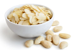 Almonds. White bowl of peeled flaked almonds on white. Spilled whole almonds Stock Photo