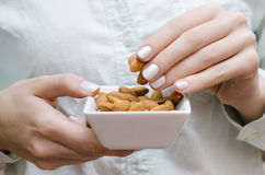 Almonds in white bowl on woman hands Stock Photo