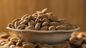 Almonds in white bowl on wooden background.  Stock Photo