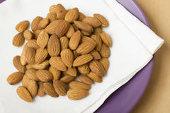 Almonds on a white napkin. Whole almonds are laid out on a plate. It is a useful product the containing calcium and vitamin E Royalty Free Stock Photography